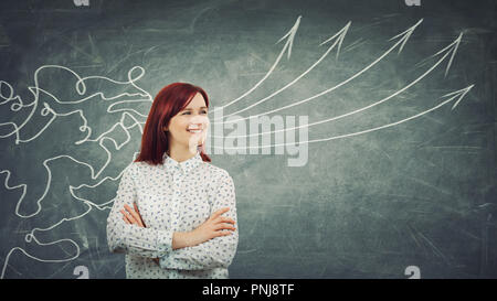 Concept of information processing as a concentrated redhead woman smiling in front of a huge blackboard as mesh lines come through head and transform  - Stock Photo