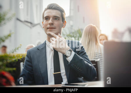Young pensive businessman sitting next to laptop and touching his chick. - Stock Photo