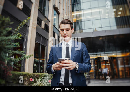 Close up of businessman next to skyscraper looking at screen of mobile phone. - Stock Photo