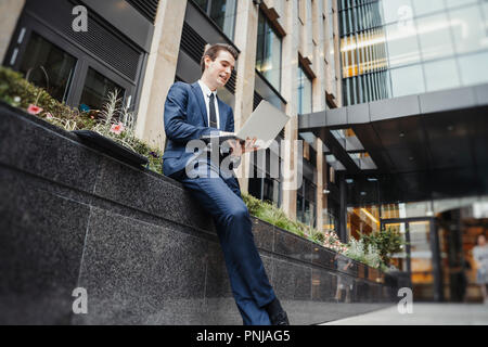 Businessman working on laptop next to skyscraper at downtown. - Stock Photo
