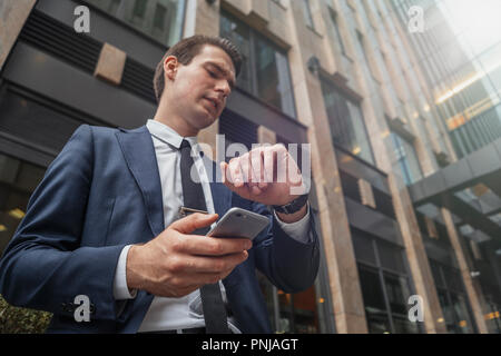 Close up of businessman holding mobile phone in hand and looking at watches. - Stock Photo