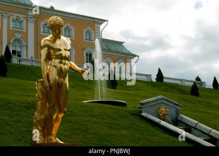 Gilded statue of Capitoline Antinous against grassy slope with fountain and Big Peterhof Palace in Saint-Petersburg, Russia, 18th century landmarks - Stock Photo