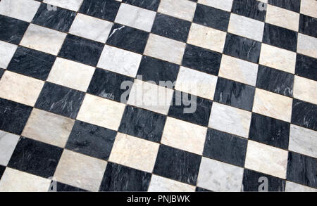 Antique checkered marble floor, black and white tiled background, diagonal view - Stock Photo