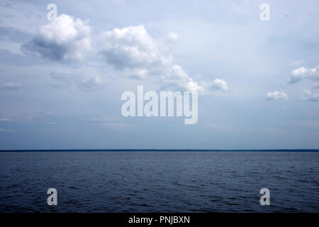 Beautiful picturesque seascape in gentle tones with clouds and coastline on the horizon - Stock Photo