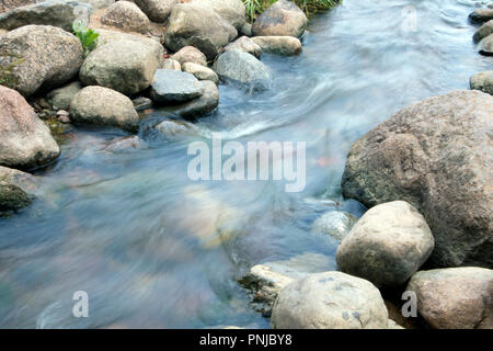 Small creek with stony bottom, rapid stream running between boulders, smoothed water surface