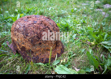 Old rusty german helmet of the Second World War with holes and cracks lying on the grass - Stock Photo