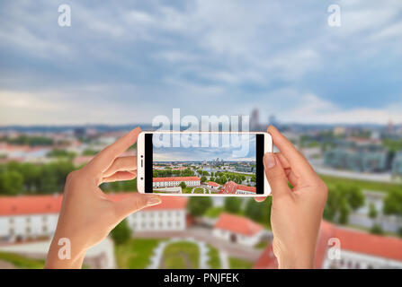 A tourist is taking a photo of Aerial panoramic view of the capital of Lithuania - Vilnius on a mobile phone - Stock Photo