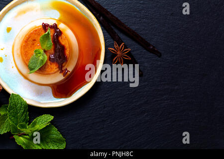 Food Dessert concept homemade vanilla Caramel custard or panna cotta with vanilla beans and spices on black stone background