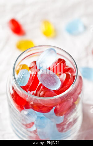 colorful candies in glass jar closeup on white paper background - Stock Photo