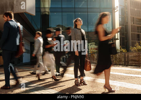 Businesswoman holding her hand bag standing still on a busy street with people walking past her using mobile phones. Woman standing amidst a busy offi - Stock Photo