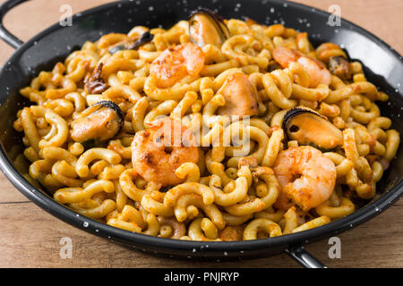 Traditional Spanish fideua. Noodle paella on wooden table Stock Photo