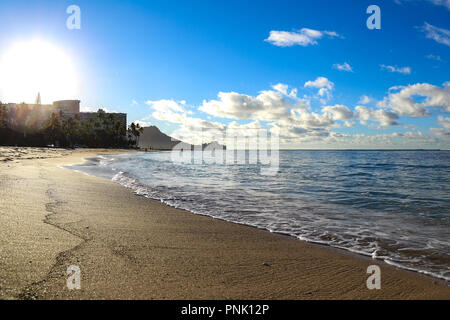 Morning sun rising over quiet and serene Waikiki beach on a sunny summer day with blue sky and scattered white little clouds - Stock Photo