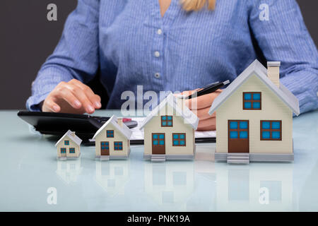 Row Of Increasing House Models In Front Of Businesswoman Calculating Invoice On Desk - Stock Photo