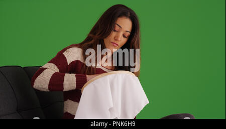 Latina woman sitting on couch embroidering fabric on green screen - Stock Photo