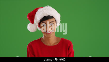Smiling African-American woman in Christmas attire on green screen - Stock Photo