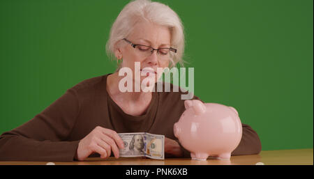 Elderly woman about to put 100 dollar bill into piggy bank on green screen