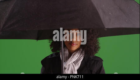 Pretty African American woman holding umbrella looking at camera on green screen - Stock Photo