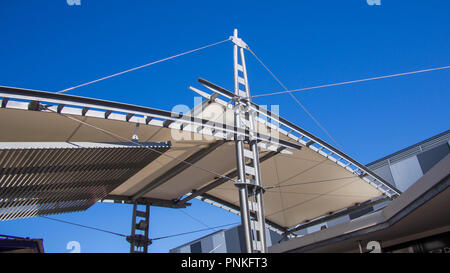 Sail shade pergola made of galvanized steel and stainless steel wire cable tall structure against the blue sky - Stock Photo