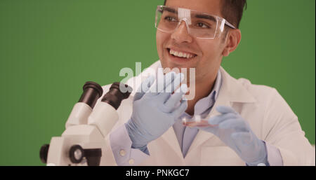 Latino scientist makes brilliant discovery in lab on green screen - Stock Photo