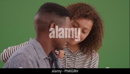 Millennial black man and woman look at each other lovingly on green screen - Stock Photo