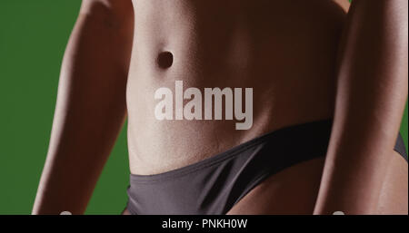 Closeup of woman's flat toned stomach on green screen - Stock Photo
