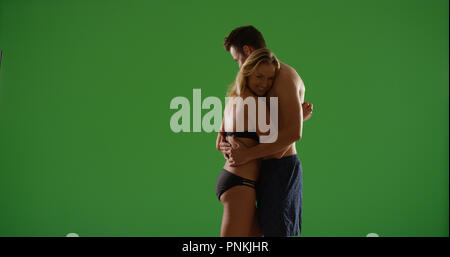 Loving white couple in swimsuits hugging at sunset on green screen - Stock Photo
