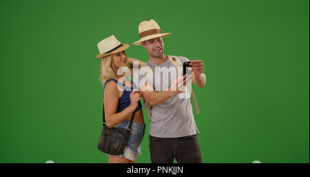 Happy white couple taking selfies while spending time together on green screen - Stock Photo