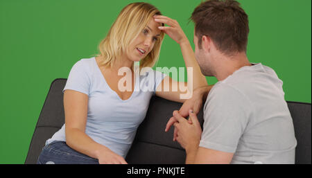 Young white couple sitting on couch having conversation on green screen - Stock Photo