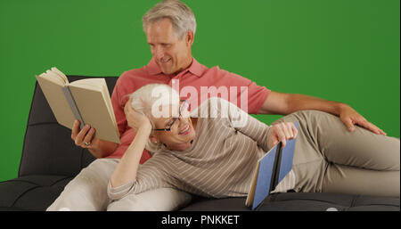 Happy senior couple reading books together relaxing on couch on green screen - Stock Photo