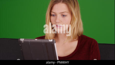 Close up portrait of cute millennial woman using tablet on green screen - Stock Photo