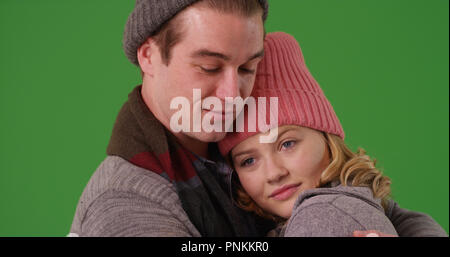 Close up of couple in winter clothes tenderly embracing on green screen - Stock Photo