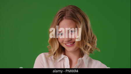 Attractive female with blonde hair smiling at camera on green screen - Stock Photo