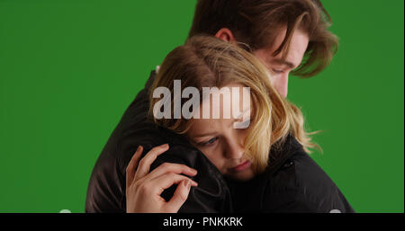 Young white couple hugging each other tenderly on green screen - Stock Photo