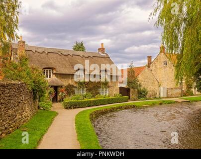 Stone-built picturesque thatched cottage in Thornton-le-Dale, North Yorkshire.  A path follows the curve of the river as it flows passed the house. - Stock Photo