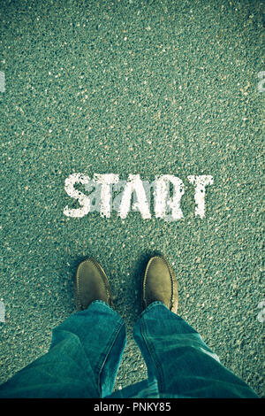 feet and legs of a man standing near the word START, conceptual image for a new beginning or competition in business - Stock Photo