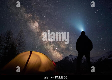 Man tourist with flashlight stands near his camp tent at night under a sky full of stars. - Stock Photo