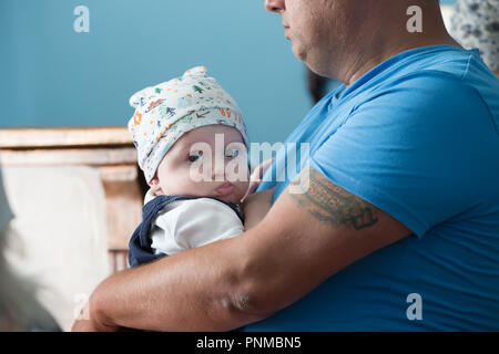 Belarus, Gomel, July 2, 2016. The Church of Zyabrovskaya. A brutal father with a tattoo on his arm holds a baby