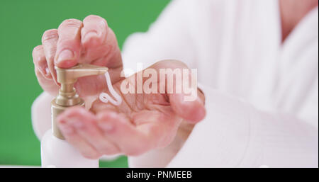 Senior caucasian woman applying lotion to hands on greenscreen background - Stock Photo