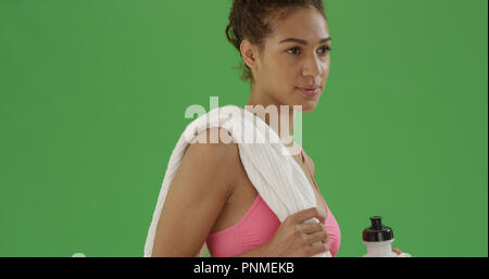 Fit African American girl in gym clothes with water bottle and towel - Stock Photo