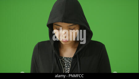 A depressed young girl in hoodie poses for a portrait on green screen - Stock Photo