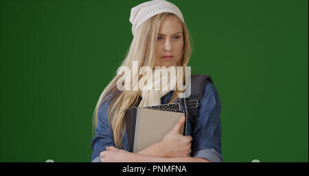 Intelligent young female student thinking to herself on green screen - Stock Photo