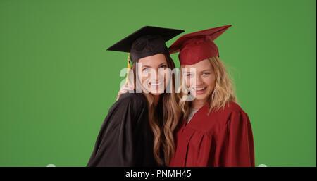 Pair of happy white female college graduates posing on green screen - Stock Photo