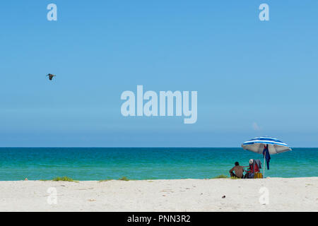 Couple under an colourful beach umbrella enjoying a day out on the beach of Chuburna, Yucatan, Mexico. Turquoise waters, calm sea. white sand. - Stock Photo