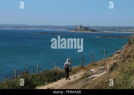 a young woman walks down a rural path along the blue sea on Cornwall coast