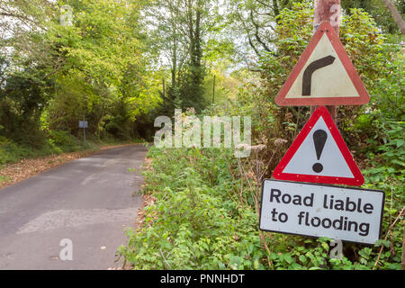 Flood warning sign on country road in England, UK - Stock Photo