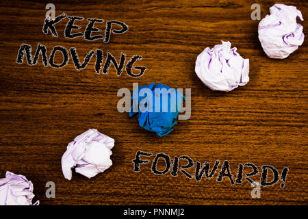 Word writing text Keep Moving Forward Motivational Call. Business concept for Optimism Progress Persevere Move Brown woody desktop four white crumpled - Stock Photo