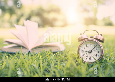 alarm clock and book in park, time for learning and reading concept. - Stock Photo
