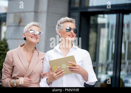 Two businesswoman walking on street near building. business woman going together with tablet computer - Stock Photo