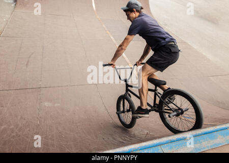 Freestyle male rider riding in skate park on bmx - Stock Photo