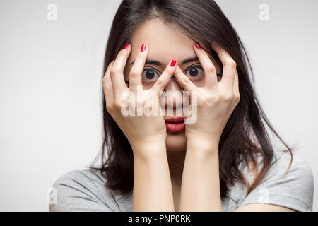 Young Asian woman covered her face with hands in fear, isolated studio shot - Stock Photo